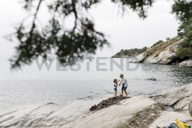 Greece, Chalkidiki, brother and little sister playing together on the beach - KMKF00163
