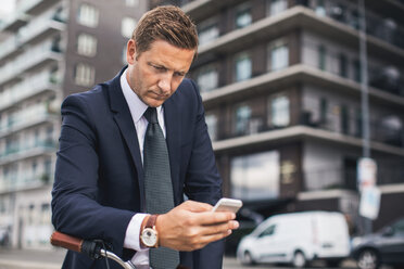 Businessman using smart phone in city - MASF05139