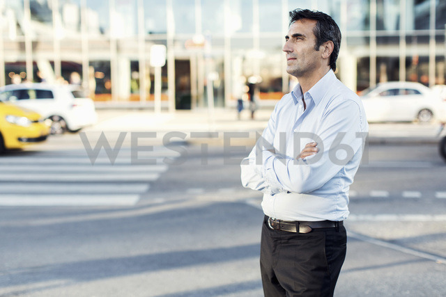 Businessman with arms crossed looking away while standing by city street - MASF05148
