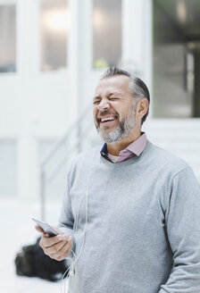 Businessman laughing while communicating through headphones in office - MASF05157