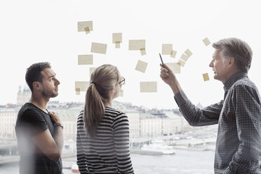 Business people discussing over adhesive notes stuck to glass window - MASF05172
