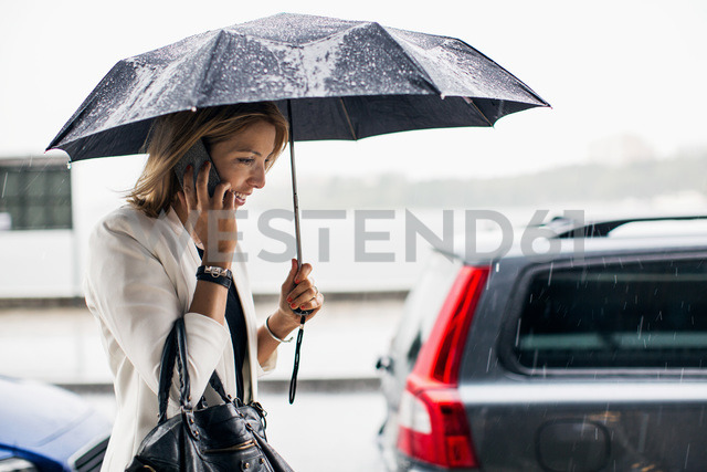 Businesswoman talking on smart phone during rainy season in city - MASF05202