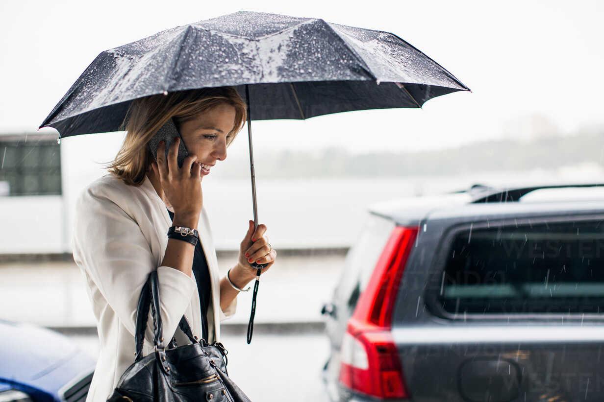 Businesswoman talking on smart phone during rainy season in city - MASF05202 - Maskot ./Westend61
