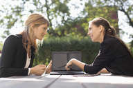 Businesswoman discussing with female colleague through laptop at outdoor cafe - MASF05208