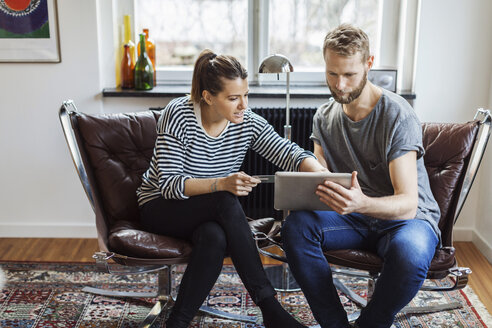 Couple shopping online while sitting on chairs at home - MASF05226