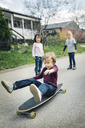 Children looking at friend skateboard on footpath outside house - MASF05232