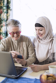 Senior woman with female home caregiver visiting bank through laptop at home - MASF05238