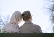 Rear view of senior woman and female home caregiver sitting together on park bench - MASF05241