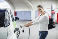 Side view portrait of playful woman electrical charger pump at gas station - MASF05262