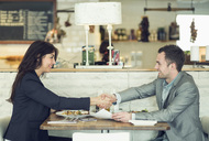 Side view of businessman and businesswoman shaking hands at restaurant table - MASF05301