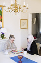 Young female home caregiver with senior woman playing ludo at home - MASF05316