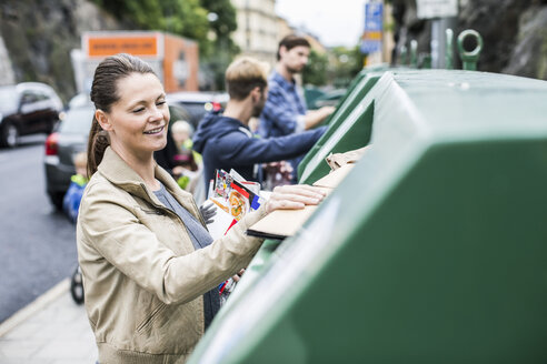 Woman and friends putting recyclable materials into recycling bins - MASF05337