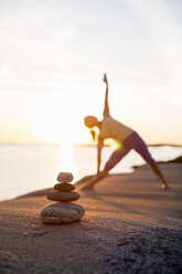 Woman practices yoga on lakeshore with focus on stack of stones - MASF05346