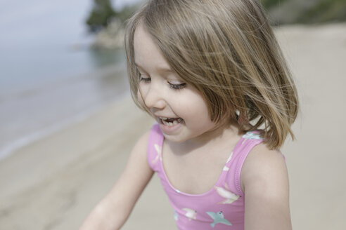 Portrait of happy little girl playing n the beach - KMKF00183