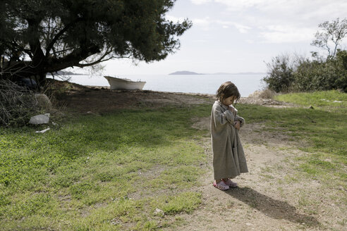 Little girl wrapped in oversized cardigan standing on a meadow - KMKF00189