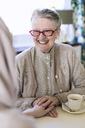 Smiling senior woman holding female home caregiver's hand at table - MASF05359
