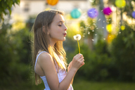 Girl blowing blowball in the garden - SARF03670