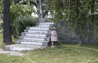 Little girl standing in garden looking up to tree - KMKF00192