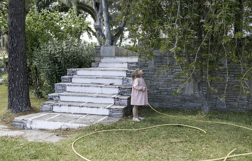 Little girl standing in garden looking up to tree - KMKF00192