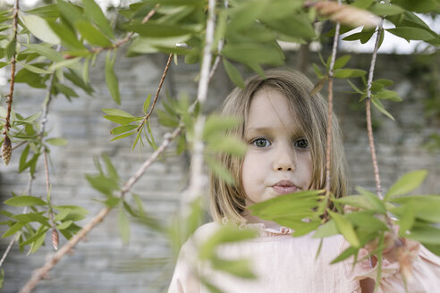 Portrait of little girl between twigs in a garden - KMKF00195