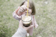 Little girl putting straw in glass of coffee - KMKF00201
