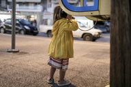 Back view of little girl using telephone booth - KMKF00204
