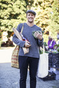 Portrait of smiling man holding groceries in market - MASF05442