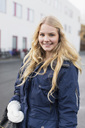 Portrait of happy teenage girl wearing winter coat on high school campus - MASF05466