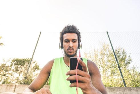 Basketball player listening music, smartphone and headphones - FMOF00336