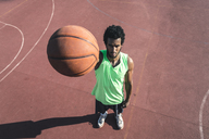 Young basketball player holding ball - FMOF00345