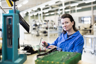 Portrait of confident female technician working on circuit board at desk in industry - MASF05472