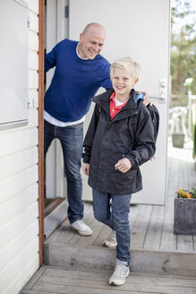 Portrait of happy boy leaving for school while father looking at him - MASF05475
