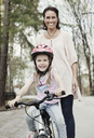 Portrait of happy girl riding bicycle while mother standing behind her on road - MASF05484