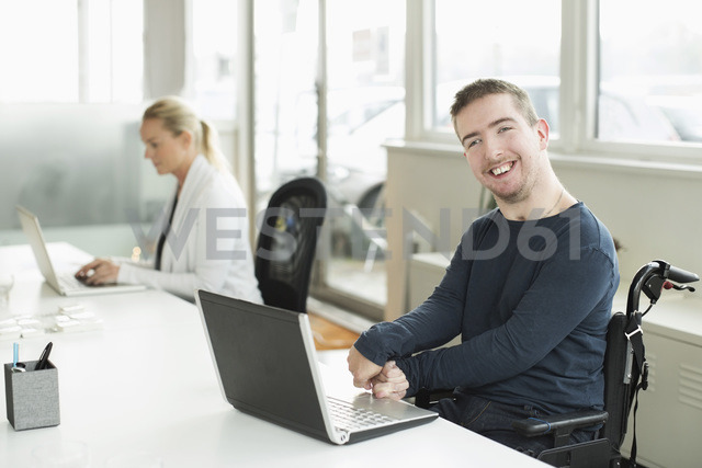 Portrait of happy businessman with cerebral palsy using laptop in office - MASF05496