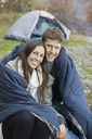 Portrait of happy couple wrapped in blanket against tent at forest - MASF05499