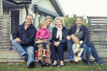Portrait of happy multi-generation family sitting together in yard - MASF05502