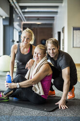 Portrait of happy instructors with senior woman at health club - MASF05511
