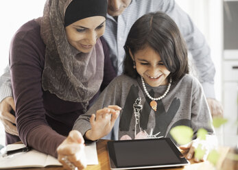 Muslim couple with daughter using digital tablet at home - MASF05535