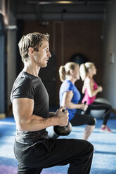 People lifting with kettlebells at health club - MASF05538