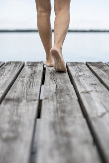 Low section of woman walking on pier - MASF05556
