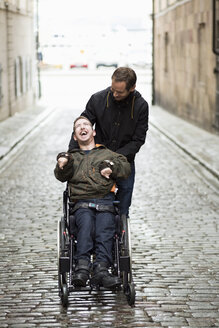 Male caretaker with disabled man on wheelchair at city street - MASF05559