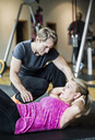 Male instructor assisting senior woman in doing sit-ups at gym - MASF05565