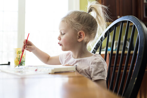 Girl painting by table at home - CAVF43043