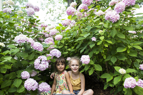 Portrait of smiling sisters sitting by flowering plants in backyard - CAVF43079