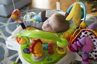 High angle view of baby boy sleeping in walker at home - CAVF43103