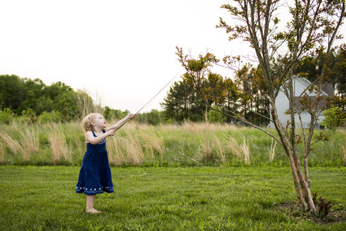 Girl playing with stick while standing on grassy field against clear sky - CAVF43121