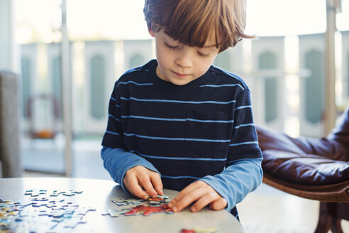 Boy solving jigsaw puzzle at home - CAVF43232