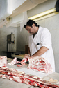 Serious butcher chopping meat at counter in shop - CAVF43394