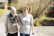 Full length of senior woman with female home caregiver walking arm in arm on street - MASF05606