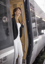 Happy businesswoman standing at train door - MASF05609